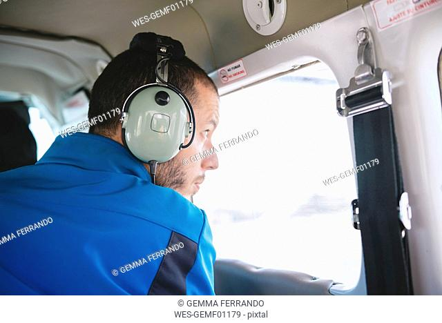 Man with headphones in light airplane looking out of window