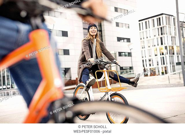 Carefree woman with man riding bicycle in the city