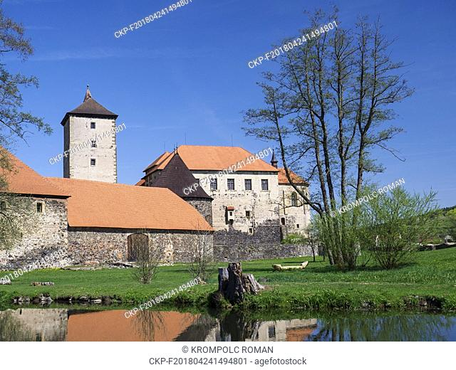 Water Castle Svihov, gothic granary behind the water canal - the Uhlava river. In the foreground on the lawn is a cluster of several trees with raking leaves...