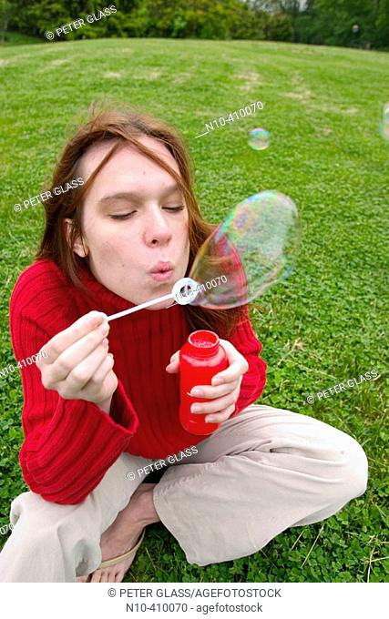 Young redhead woman sitting on the grass at a park in Connecticut, USA, blowing soap bubbles