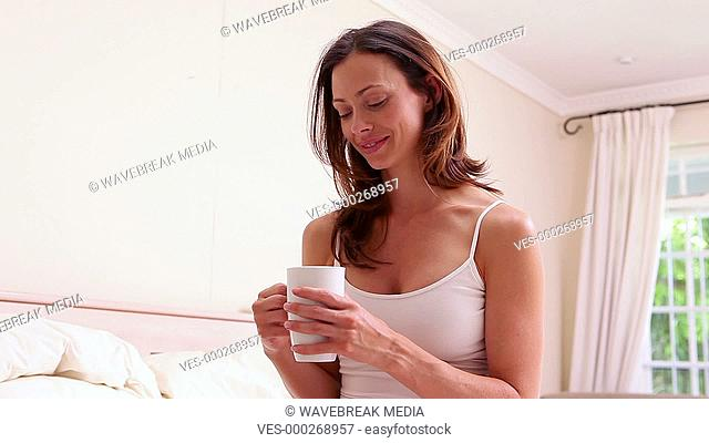 Smiling brunette drinking coffee