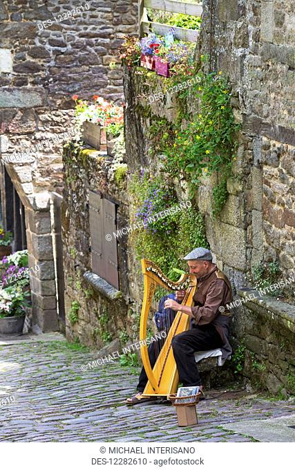 Senior man playing large wooden harp on cobblestone road along a stone wall with flowers and greenry hanging; Dinan, Brittany, France