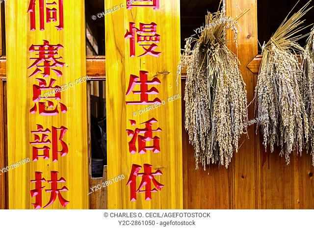 Huanggang, Guizhou, China. A Dong Ethnic Village. Inscription on a House, next to Drying Rice