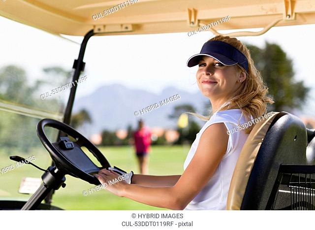 Woman driving golf cart on course