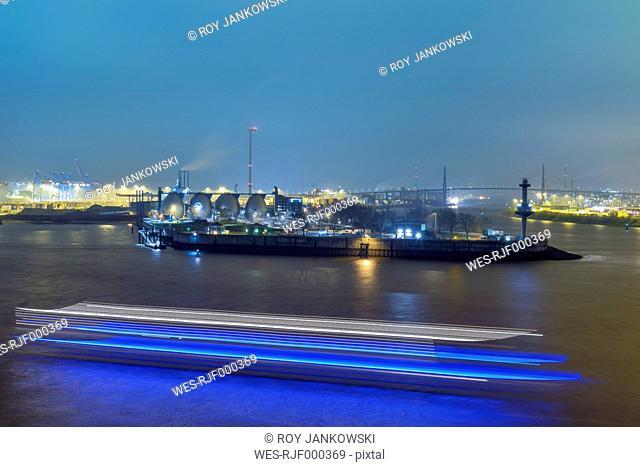 Germany, Hamburg, harbor at night with ship passing by