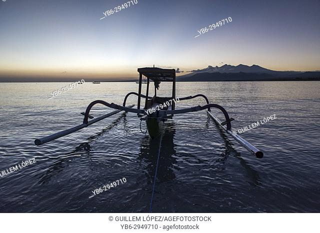 A traditional boat moored at seashore of Gili Air just before sunrise, Gili Islands, Indonesia