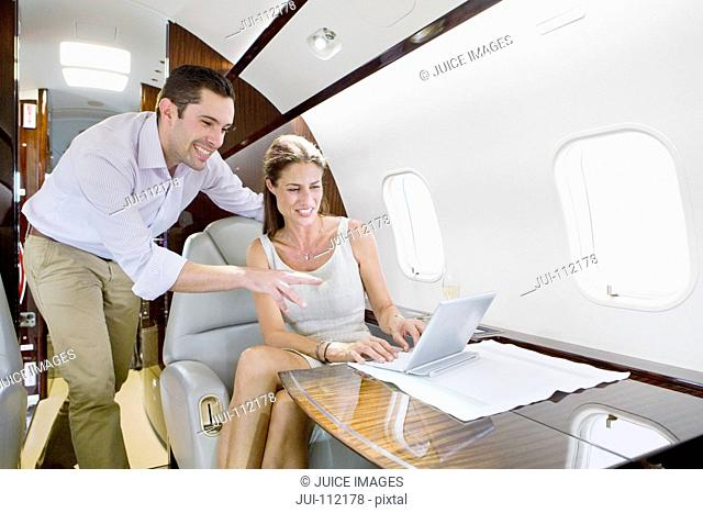 Businessman and businesswoman working on digital tablet on private jet