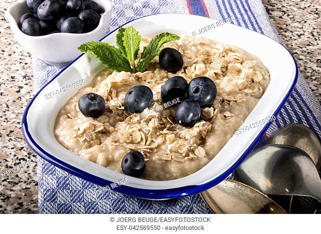 porridge made with traditional irish oatmeal in an enamel bowl with sweet blueberries and mint