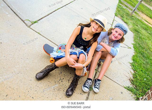 Portrait of girls sitting on skateboards