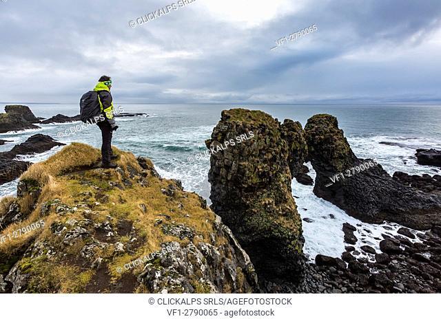 A man admires the ocean and its rocks near Arnarstapi, Snaefellsnes peninsula, Western Iceland, Europe