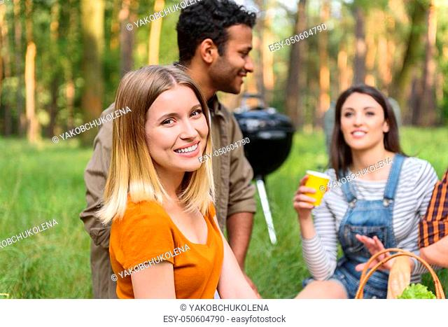 Happy young people resting in nature together. They are sitting on grass and laughing. Blond girl is looking at camera with joy
