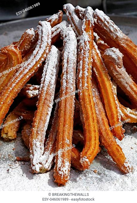 Heap of sweet fresh churros with sugar, traditional Spanish or Portuguese deep fried dough pastry snack cooked close up, high angle view