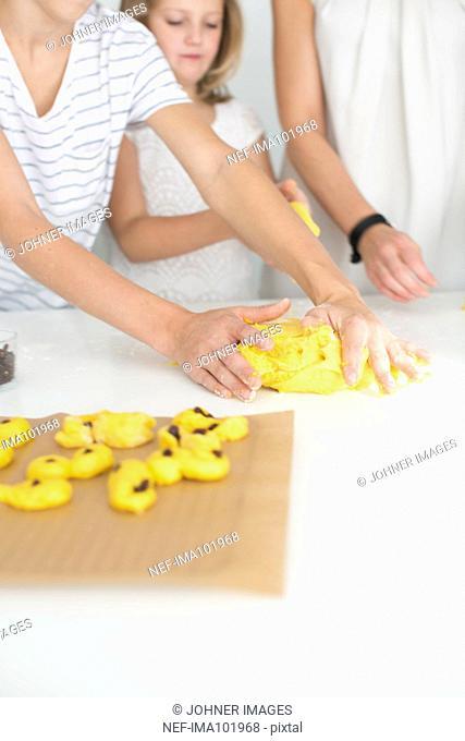 Mother and kids preparing saffron rolls