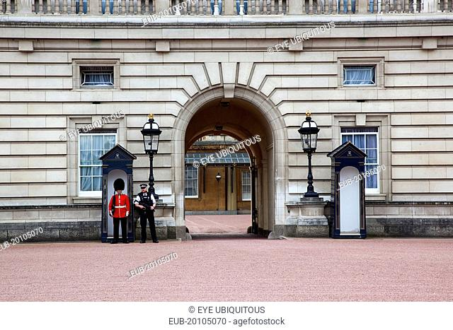 Westminster Buckingham Palace exterior with both Queens Guard and Metropolitan Police armed officers