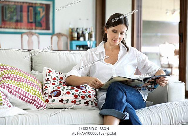 Woman sitting on sofa reading magazine