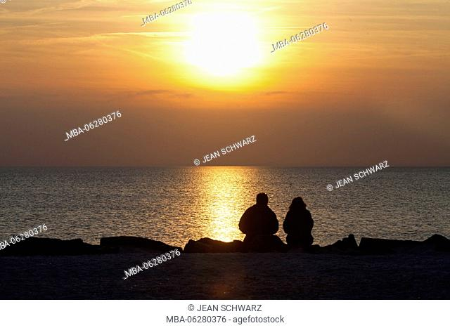 Couple watching sunset on the beach