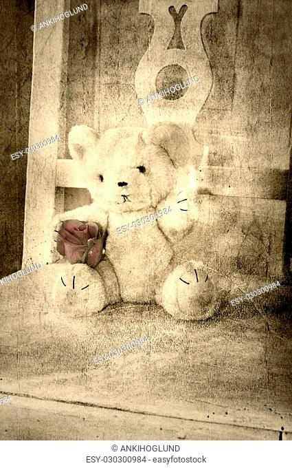 Teddy bear with rose on a chair grungy vintage style