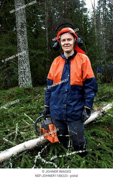 Lumberjack woman standing in forest