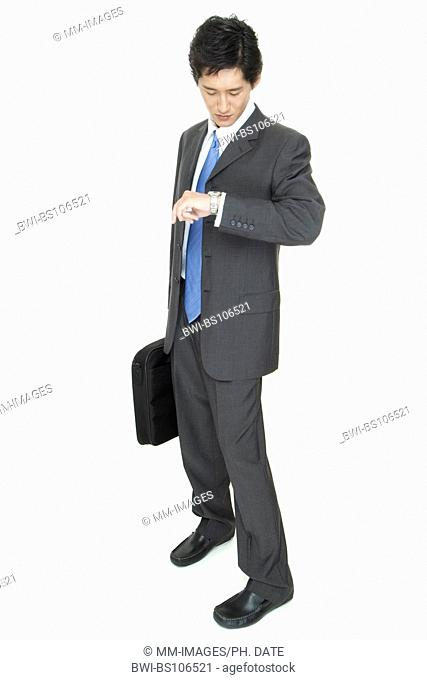 an Asian businessman with laptop case checks his watch