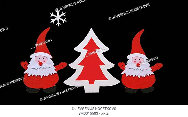 Drawing of Santa Claus and Christmass tree made of glued pieces of felt and plywood on a black background, hand-made