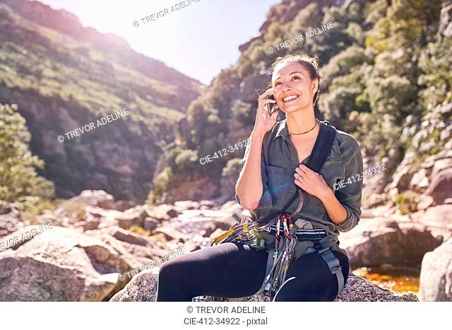 Young woman talking on cell phone below sunny, craggy cliffs