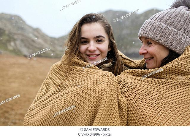 Portrait carefree mother and daughter wrapped in a blanket on snowy winter beach
