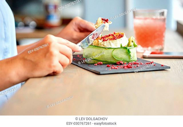 food, culinary, haute cuisine and people concept - woman eating goat cheese salad with vegetables and dried raspberries using fork and knife at restaurant or...