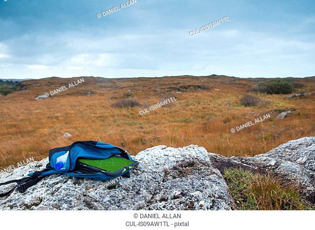 Digital tablet in backpack lying on rock, Connemara, Ireland
