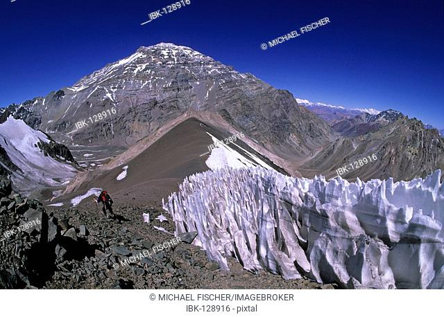 Female climber near a penitentes field with Aconcagua westface in the background Mendoza Argentina