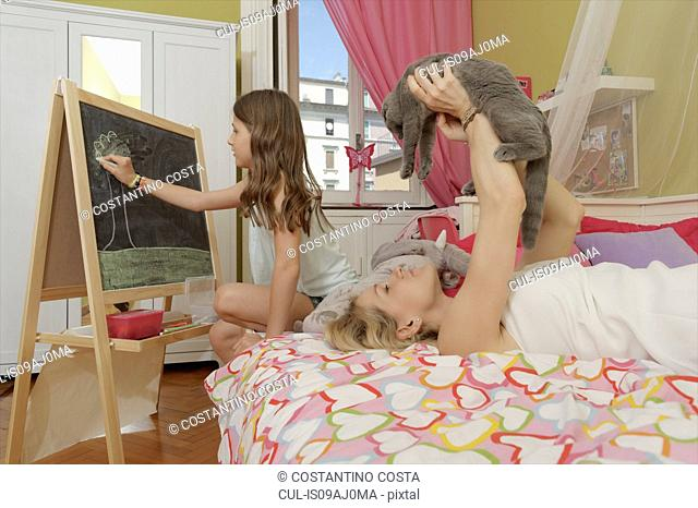 Girl drawing on blackboard whilst mother on bed with cat