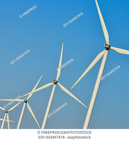 Windmills for electric power production on blue sky, France, Europe