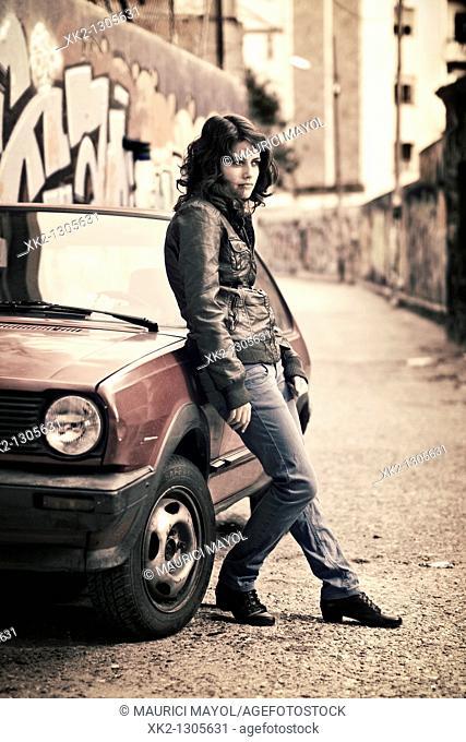 Chica apoyada en un coche retro posicion femme fatale