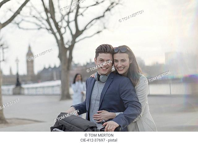 Portrait smiling, hugging couple tourists with bicycle in urban park, London, UK
