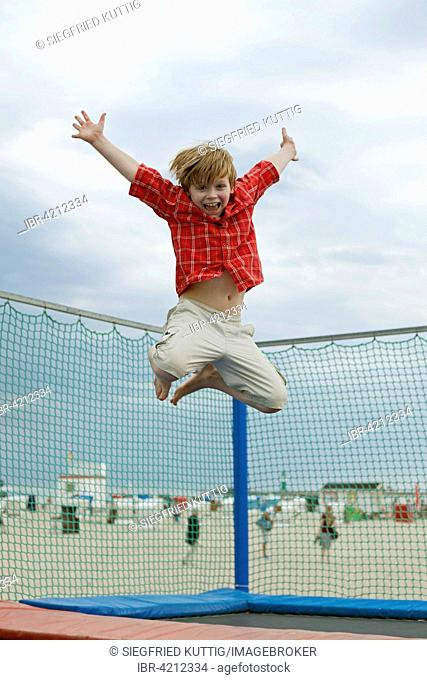 Boy jumping on trampoline, Warnemunde, Rostock, Mecklenburg-Western Pomerania, Germany