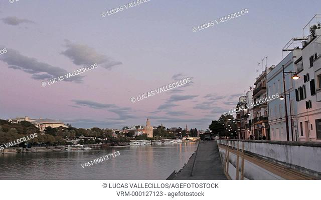 Guadalquivir river.Triana quarter at right and Gold tower. In the background towers of España square. Seville, Andalusia, Spain