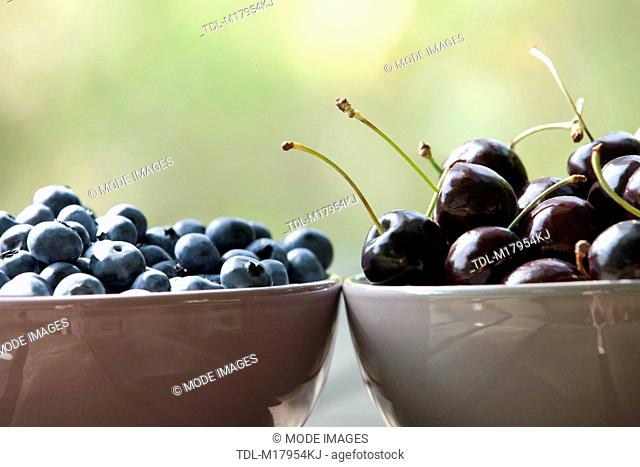 Black cherries and blueberries in ceramic bowls, close up