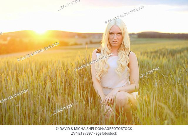 Portrait of a young woman in cornfield at sunset