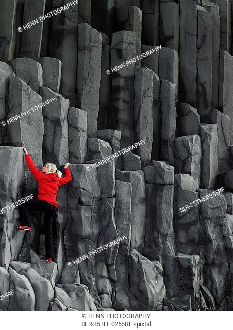 Woman climbing basalt columns