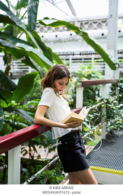 Young woman in greenhouse, reading book