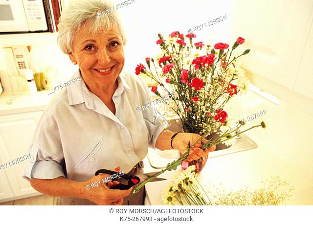 Senior woman with bouquet of flowers in kitchen