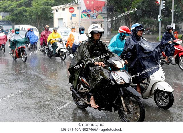 Heavy monsoon rain. Vietnamese people driving Motorbikes on Saigon Street. Ho Chi Minh City. Vietnam
