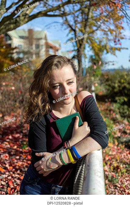 A young woman sits on a park bench clutching a book to her chest; New Westminster, British Columbia, Canada