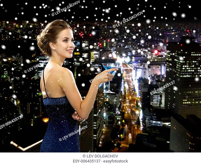 party, drinks, holidays, luxury and celebration concept - smiling woman in evening dress holding cocktail over snowy night city background