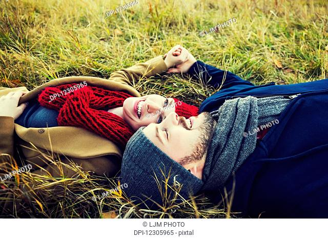 A young couple laying in the grass and holding hands in a park in autumn; Edmonton, Alberta, Canada
