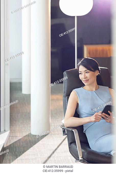 Businesswoman using cell phone in office lounge