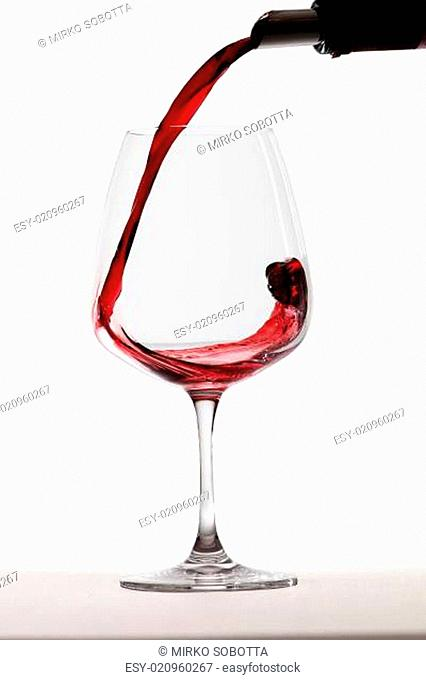 Red wine is being poured into a glass