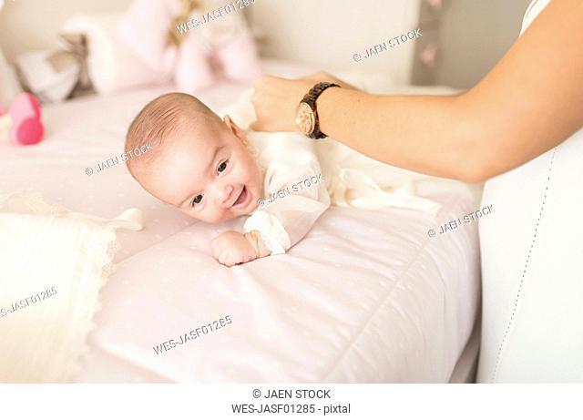 Mother dressing baby girl in Christening robe