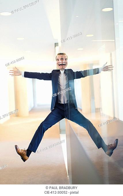 Symmetrical reflection portrait of businessman with arms and legs outstretched in office corridor