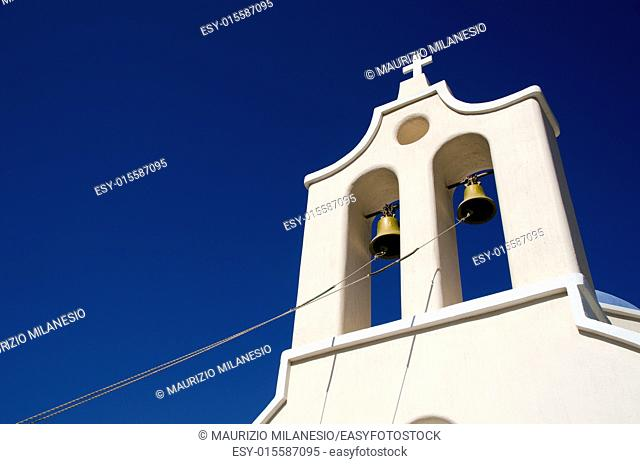 Ropes attached to the bells of a bell tower in front of the blue sky of a church in Santorini Greece