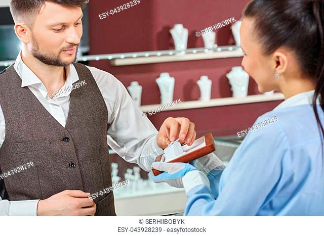 Helping to choose. Young man taking an engagement ring professional jeweler is showing him man buying jewelry at the store consumerism customer people sale...